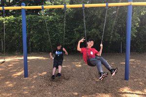 Two boy camp members swinging