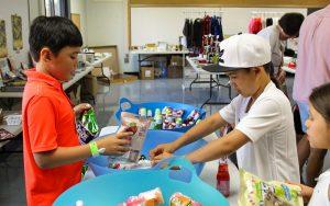 Three camp kids grabbing snacks